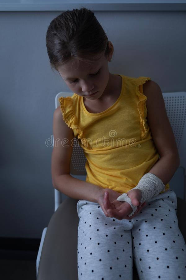 Girl sitting with fractured hand in clinic at hospital. Front view of sad Caucasian girl sitting with fractured hand in clinic at hospital royalty free stock images