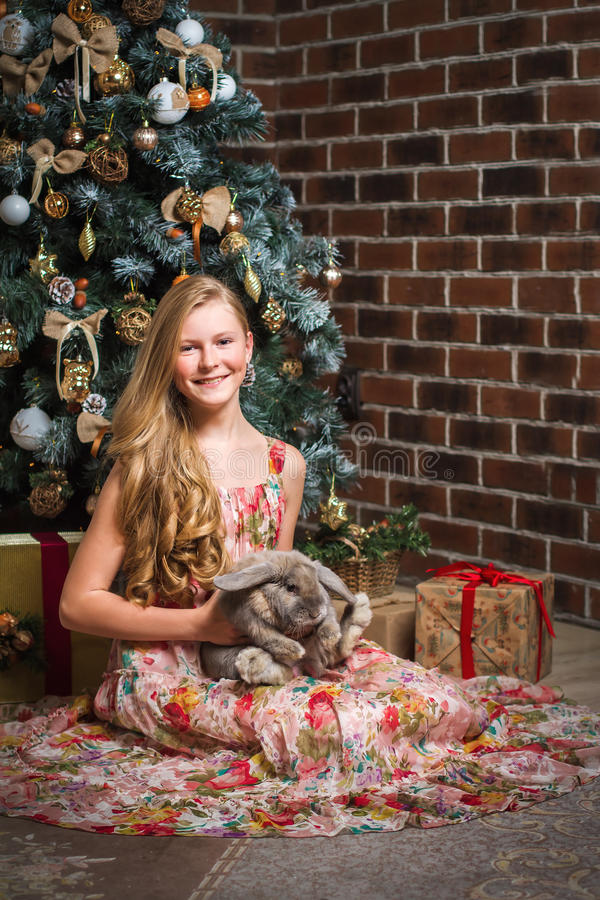 Girl sitting in front of a Christmas tree with a rabbit stock photography