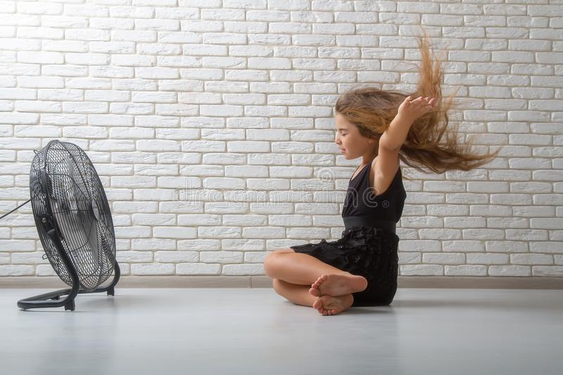 The girl is sitting in front of the fan. Little girl struggling with heat and sitting in front of a fan with flying hair in an apartment on a bricky light wall royalty free stock photography