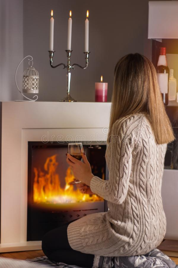 Girl sitting in front of the fireplace and warming with red wine glass in hands royalty free stock photo