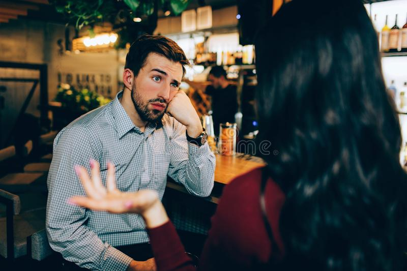 Girl sitting in front of young guy and talking to him. He looks bored. Man is not interested in conversation at all. stock photography