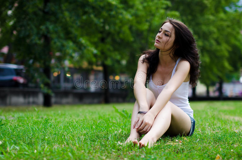 Girl Sitting In Grass Stock Images