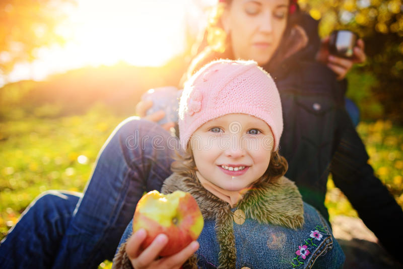 Girl sitting on the grass with an apple in his hand stock photos