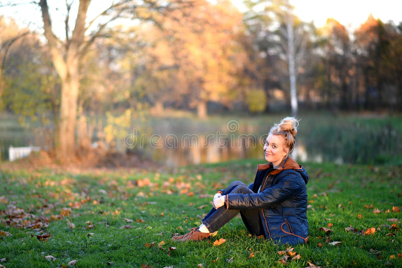 Girl sitting on the grass stock images