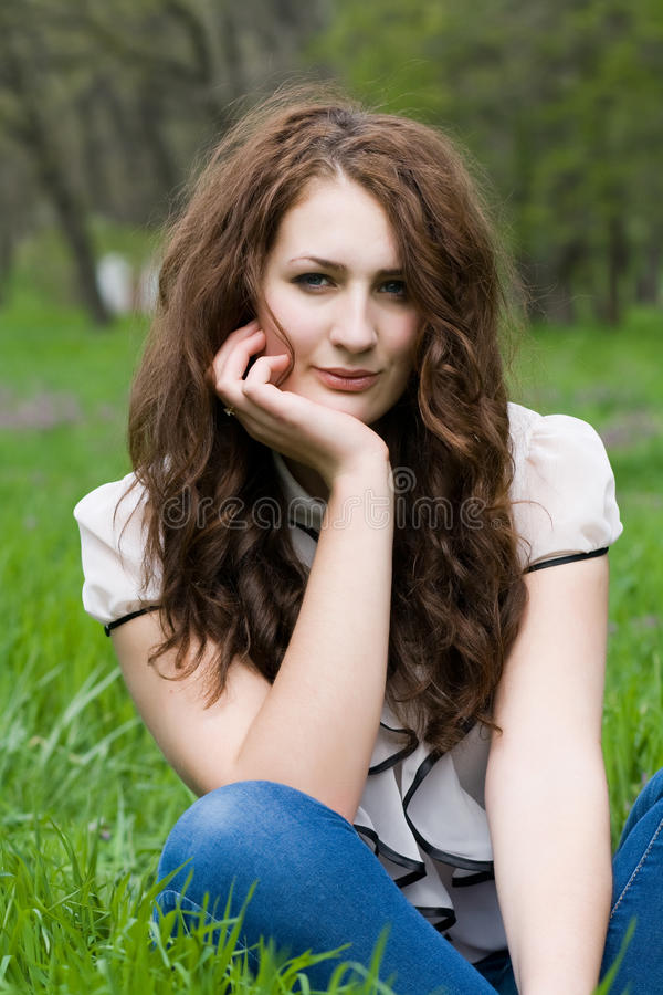 Girl sitting in the grass royalty free stock photography
