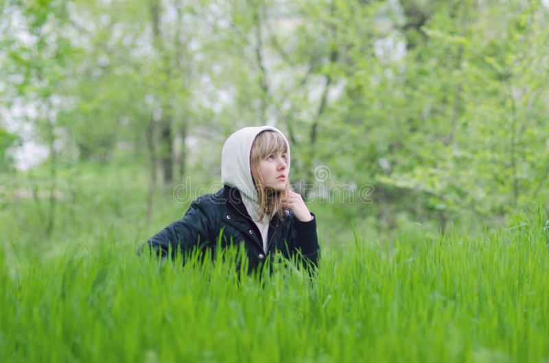Girl is sitting in the grass in the forest glade stock photos