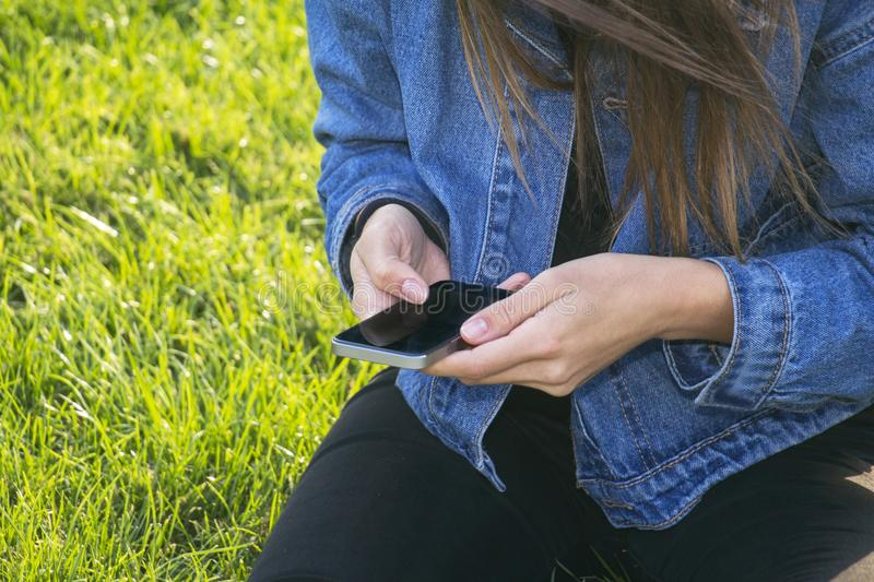 Urban lifestyle. Girl sitting on a grass and looks in the phone stock photography