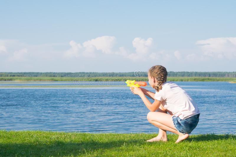 The girl is sitting on the green grass and playing with a water pistol, against the blue sky and the lake, there is a place for an stock photography