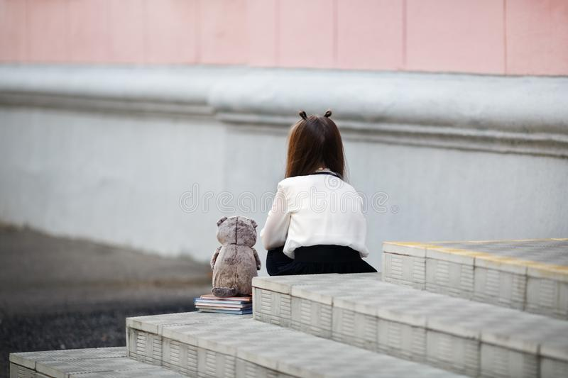Girl sitting with her back. Sad girl with a plush toy sits on the steps of the school stairs with her back to the camera. Offended child. Selective focus stock photography