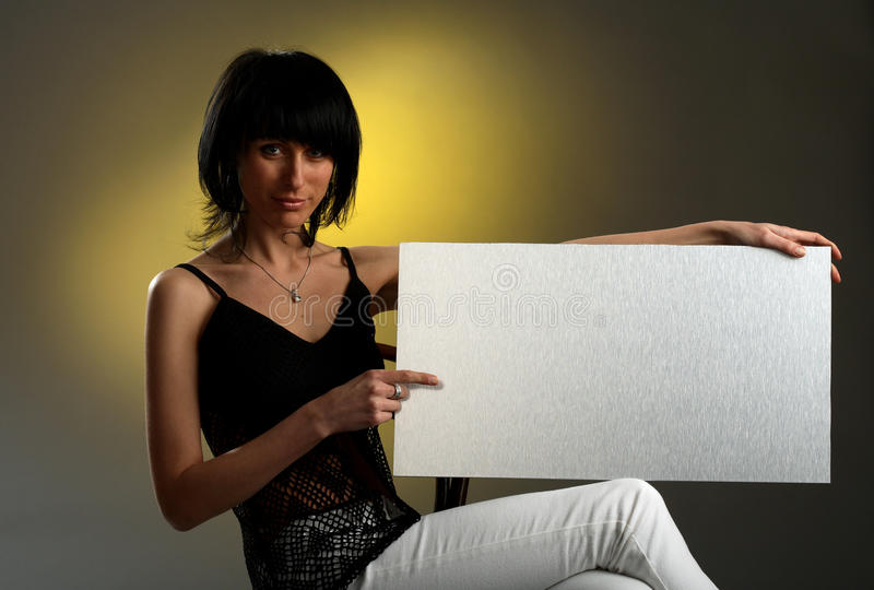 Girl is sitting and holding an empty board stock photography