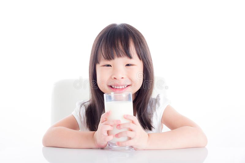 Girl sitting and holding a glass of milk over white royalty free stock photography