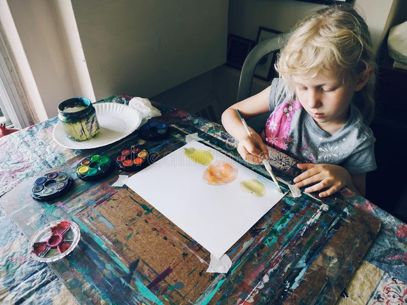 Girl sitting in home art studio concentrated on painting fruits with brushes and watercolor paints. Caucasian preschooler girl sitting in art studio concentrated royalty free stock photo