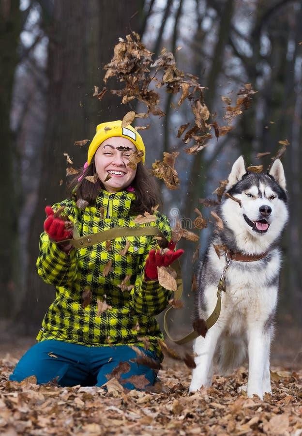 Girl sitting with husky dog stock image