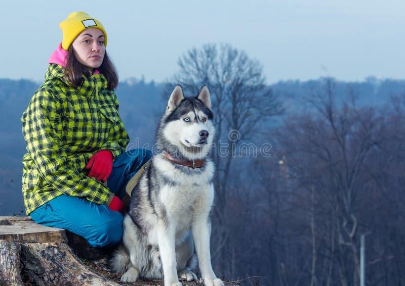 Girl sitting with husky dog stock photos