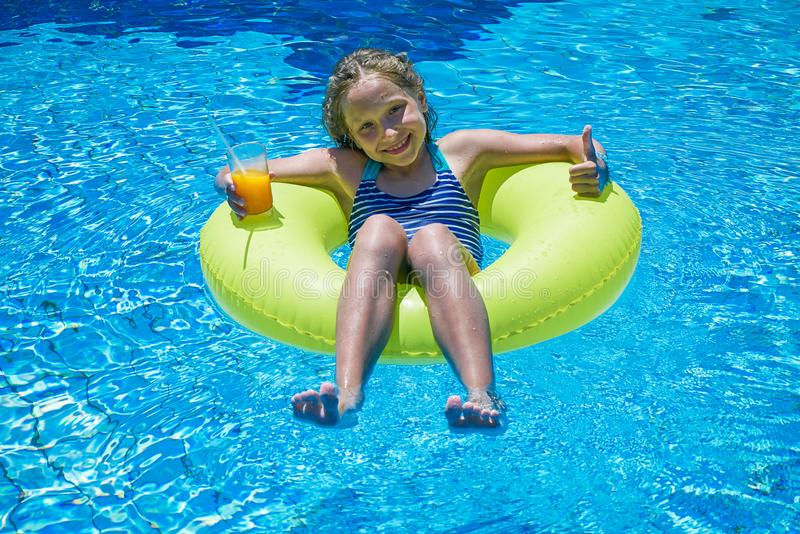 Girl sitting in inflatable ring in swimming pool with cold drink stock photo