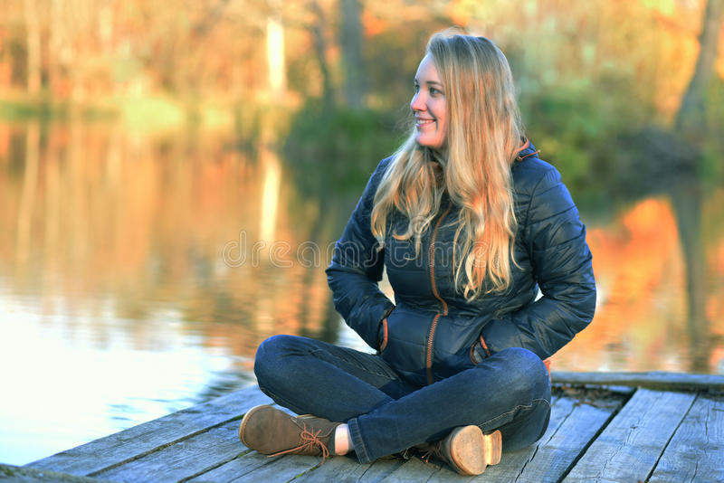 Girl sitting on the Lake Shore stock images