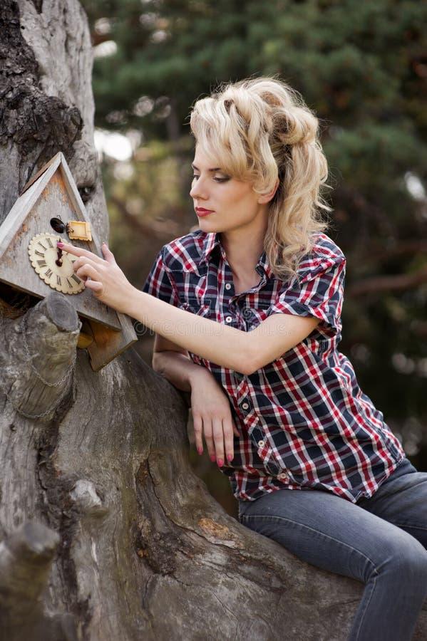 Girl sitting on large old stump stock photos