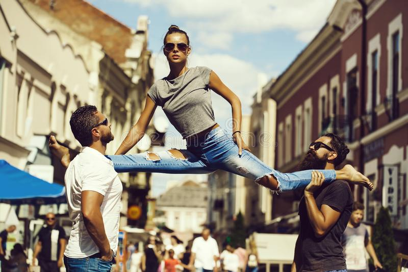 Girl sitting leg split on shoulders of two men. Girl or pretty woman, fit model, in stylish sunglasses and blue jeans sitting leg split on shoulders of two royalty free stock photography