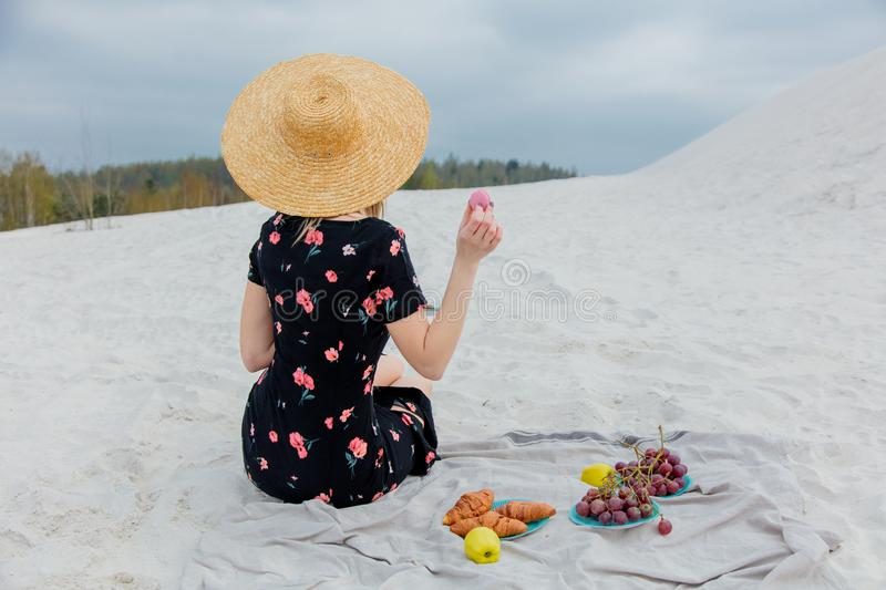 Girl sitting on litter and hold a macron in a hand. Back side view. Beach location royalty free stock image