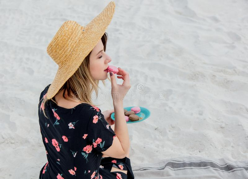 Girl sitting on litter and hold a macron in a hand. Back side view. Beach location stock photography