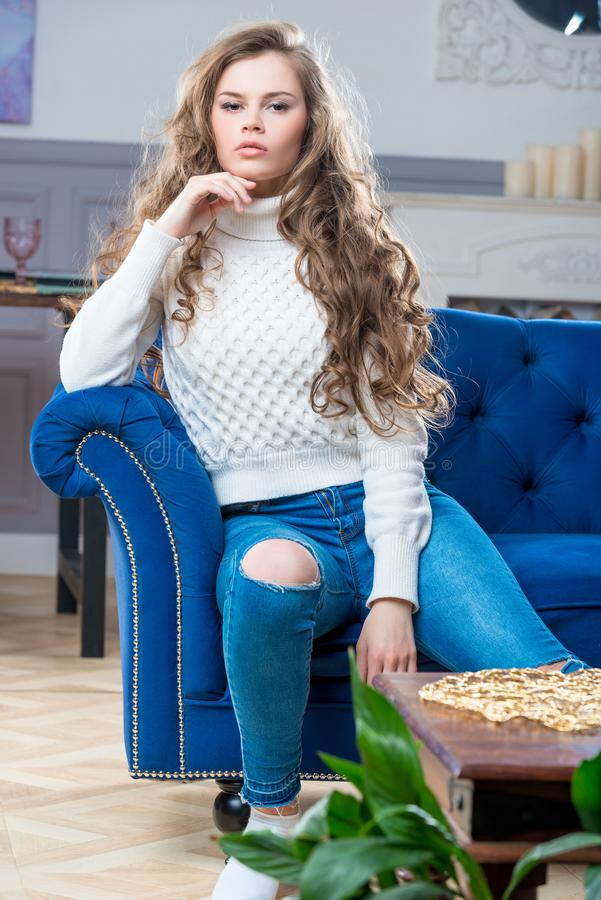 Girl sitting in living room on blue couch royalty free stock photography