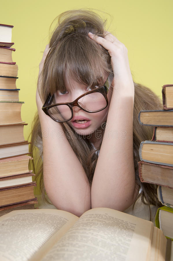 Girl sitting with lots of books and grabs his head. Age of child 10 years. Studio photography in the interior royalty free stock images