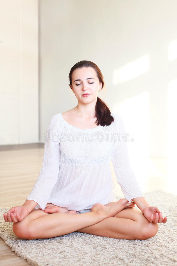 The girl sitting in the Lotus position. Beautiful girl sitting in the Lotus position royalty free stock photography