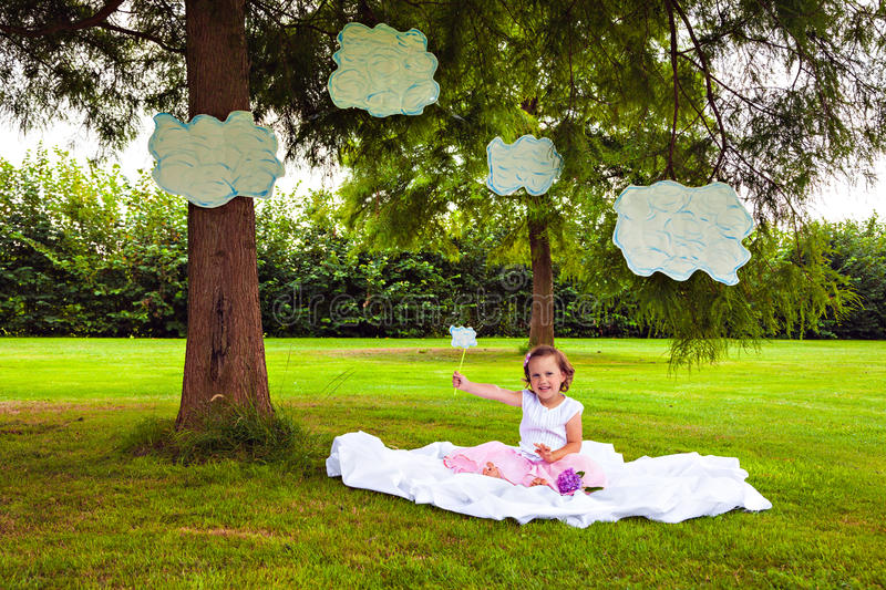 Girl sitting on the meadow with clouds. Little girl sitting on the meadow with clouds stock image