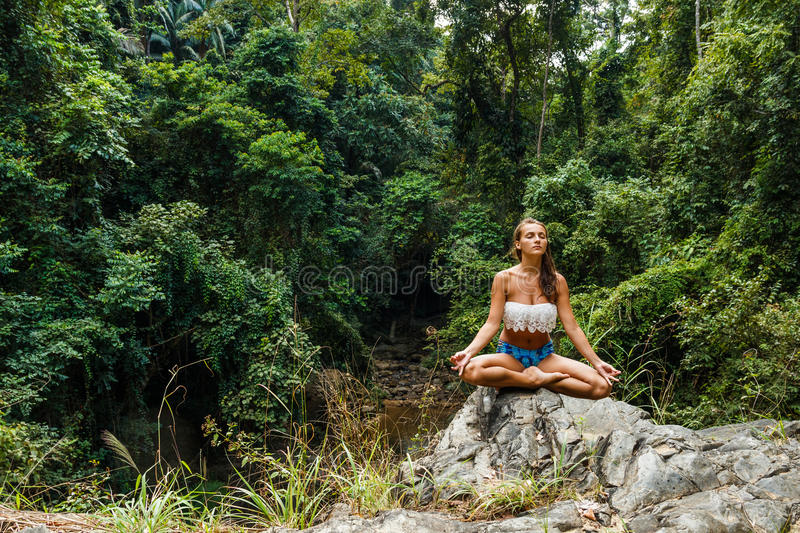 Girl sitting and meditating in forest on rock stock photo