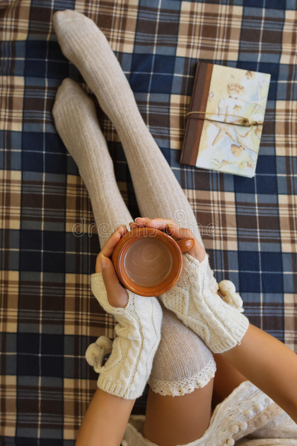 Girl, sitting in the morning on the bed, in knee-height socks an stock images