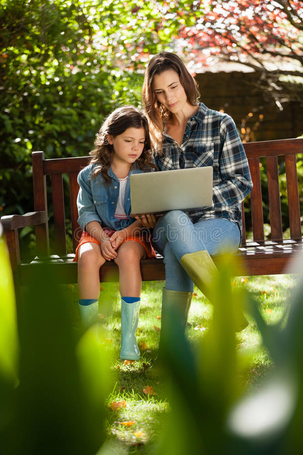 Girl sitting by mother using laptop on wooden bench stock image