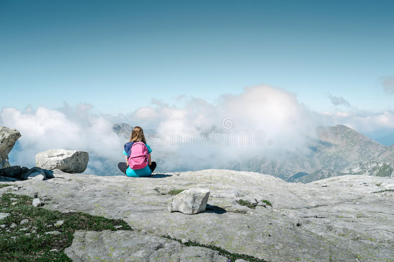 Girl sitting on the mountain stock images