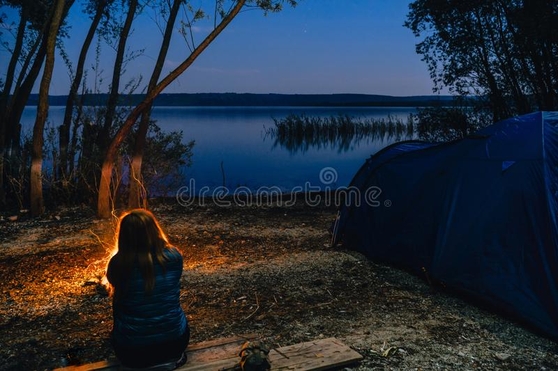 Girl is sitting near bonfire. Blue Camping Tent Illuminated Inside. Night Hours Campsite. Recreation and Outdoor. Lake. hiking,. Vacation, active life style stock photo