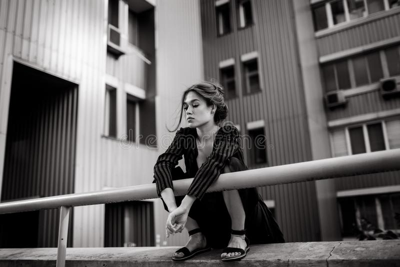 Girl sitting near the building stock images