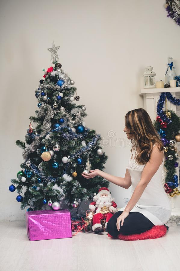 Young happy beautiful woman with gift boxes sits near decorated Christmas tree in the room of the house. Young beautiful woman in royalty free stock image