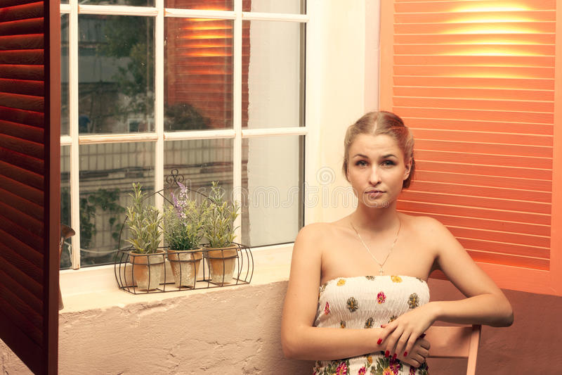 Girl sitting near an open window