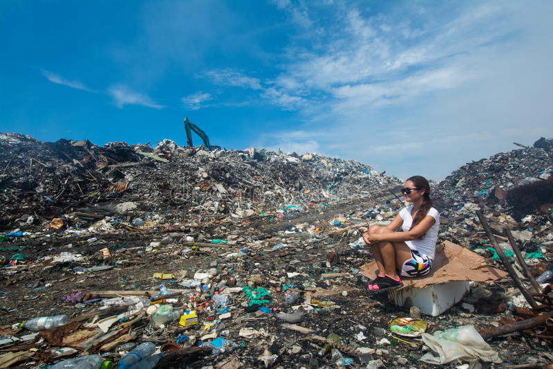 Girl sitting on trash near the road at garbage dump stock images