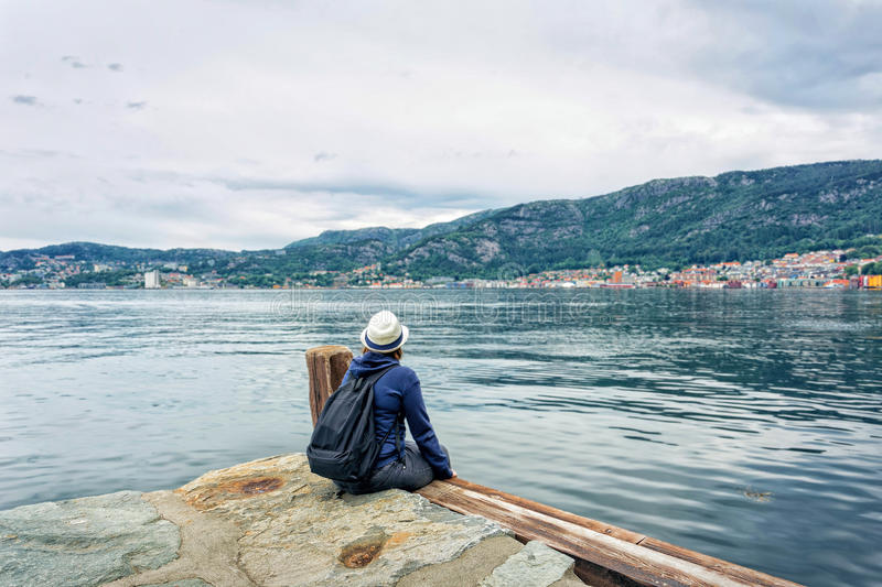 Girl sitting near the sea alone. In Bergen, Norway royalty free stock photography