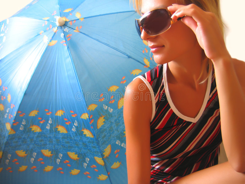 Girl sitting near an umbrella