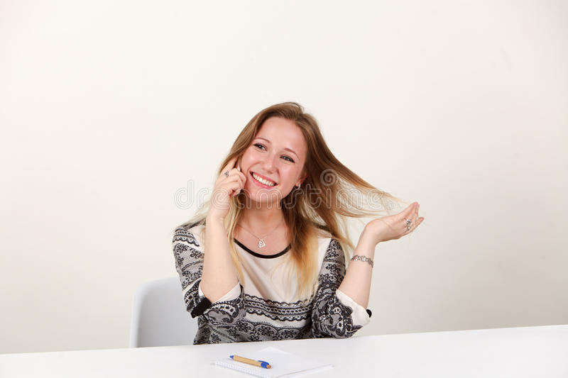 A girl is sitting in the office and emotionally talking on the phone royalty free stock photography