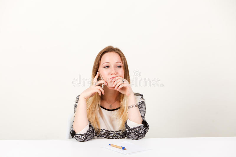 A girl is sitting in the office and emotionally talking on the phone royalty free stock photos