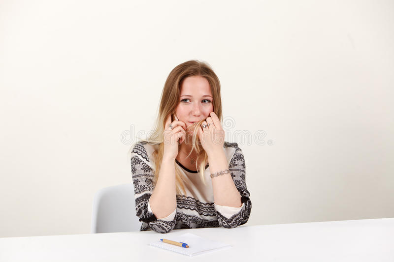 A girl is sitting in the office and emotionally talking on the phone stock photos