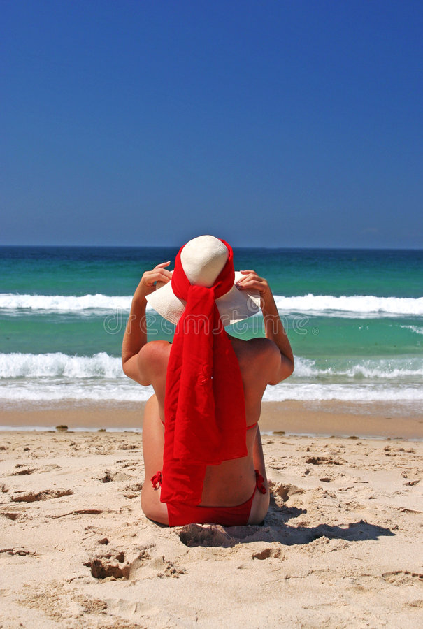 Free Girl Sitting On Sandy Beach In The Sun Adjusting Hat. Blue Sky, Blue Sea Red Scarf. Spain. Stock Image - 124741