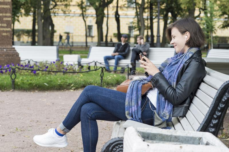 Girl sitting on a Park bench in white headphones looking at phone and smiling, Russia, St. Petersburg, September, 2018 royalty free stock photography