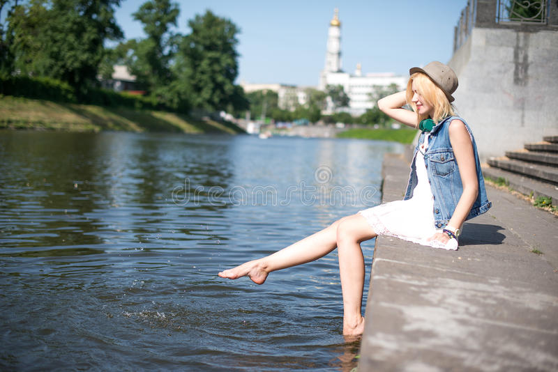 Girl sitting at the pier and hanging bare feet. Water splashes royalty free stock images