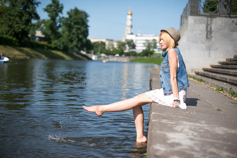Girl sitting at the pier and hanging bare feet. Water splashes royalty free stock photo