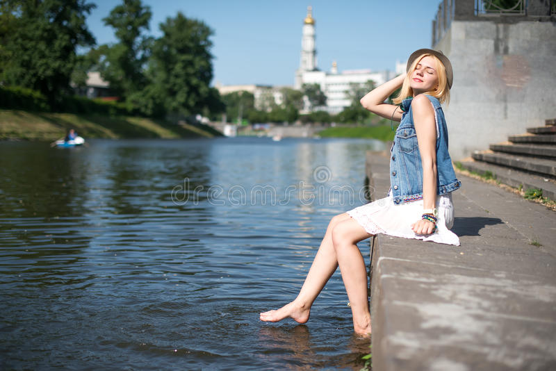 Girl sitting at the pier and hanging bare feet. Water splashes stock photography