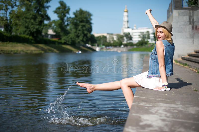 Girl sitting at the pier and hanging bare feet. Water splashes royalty free stock image