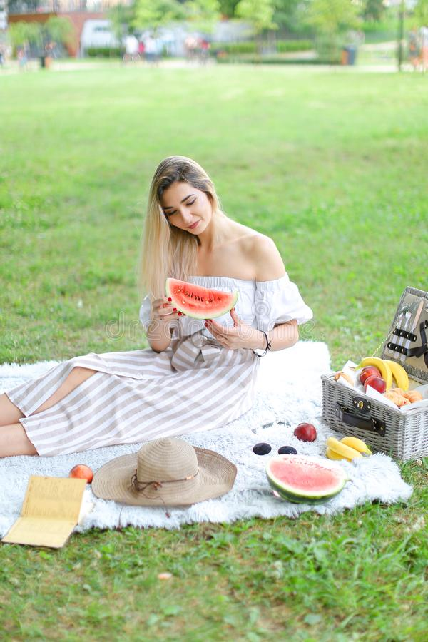 Girl sitting on plaid near fruits and hat, eating watermelon, grass in background. royalty free stock photography