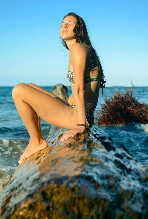 Girl sitting on a plank in the water stock photo